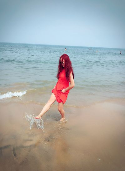 Full length of young woman splashing water on shore