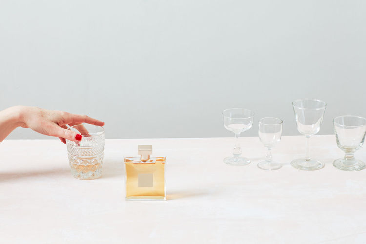 Midsection of woman holding glass bottle on table