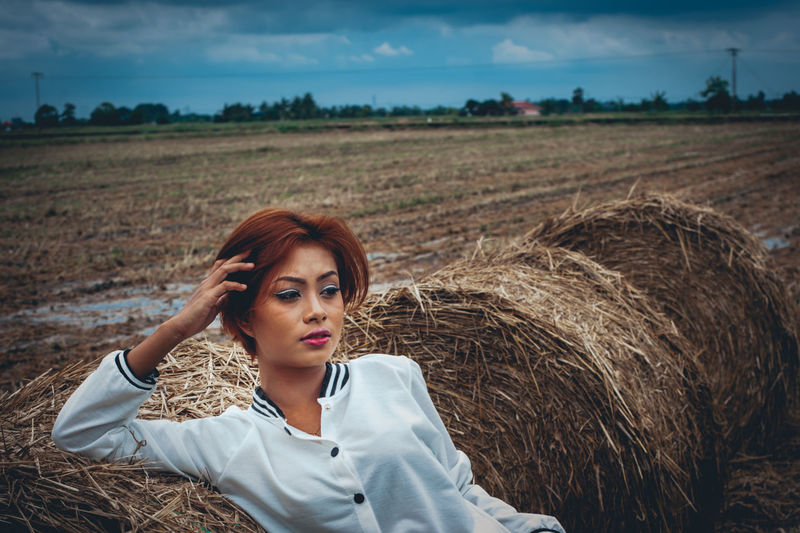 Thoughtful woman sitting on hay bale at field