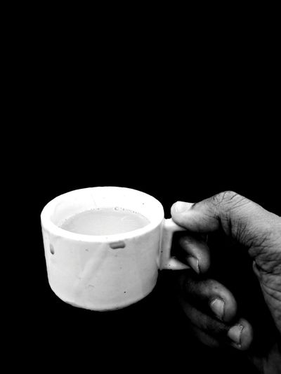 Man holding coffee cup against black background