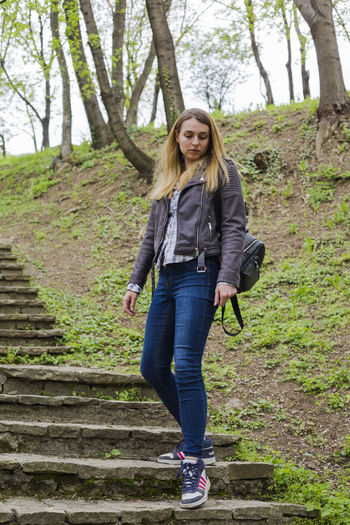 One Person Full Length Tree Casual Clothing Portrait Looking At Camera Hair Plant Young Adult Smiling Front View Staircase Day Long Hair Jacket Blond Hair Clothing Leisure Activity Forest Hairstyle Jeans Outdoors Steps And Staircases Beautiful Woman