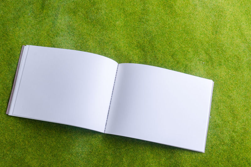 Directly Above Shot Of Open Notebook On Grass