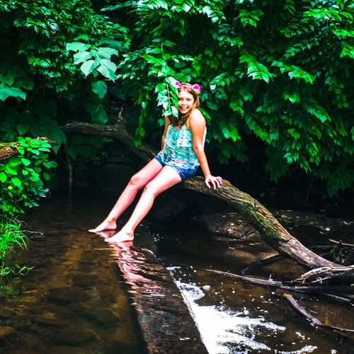 Smiling girl sitting on trees