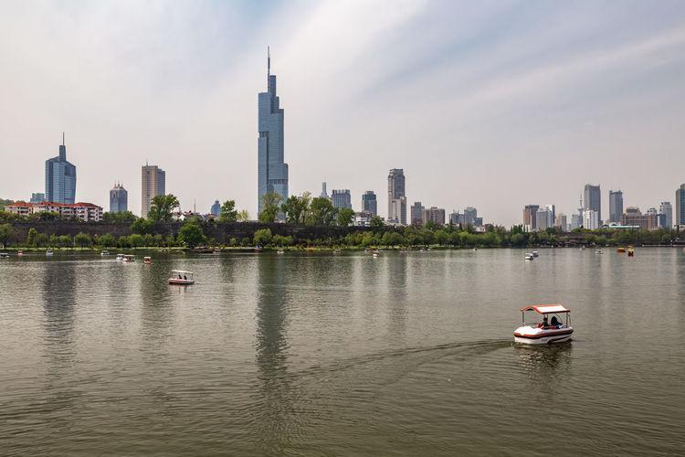 Nautical vessel on sea against modern buildings in city
