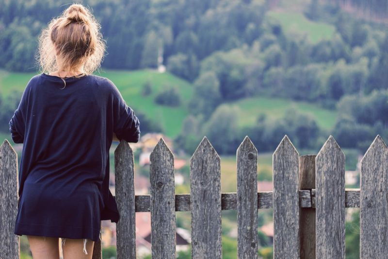 Rear view of young woman standing by fence