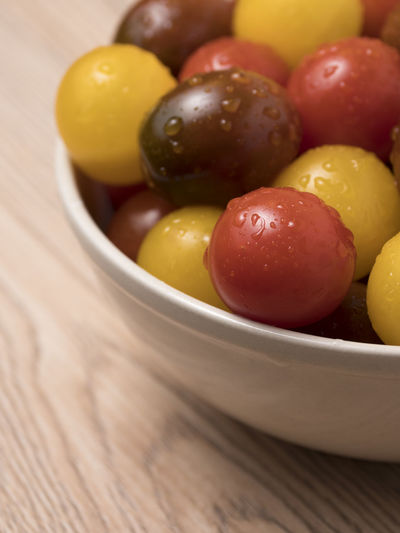 Cherry tomatoes in a variety of colors in ceramic bowl on wooden background. Fresh; Food; Healthy; Ripe; Red; Vegetable; Cherry; Tomato; Vegetarian; Yellow; Diet; Orange; Variety; Colorful; Different; Health; Green; Organic; Ingredient; Many; Summer; Small; Juicy; Raw; Nature; Tomatoes; Color; Natural; Closeup; Background; Agricul Food Food And Drink Fruit Healthy Eating Wellbeing Bowl Freshness Olive Close-up Indoors  Wood - Material Still Life No People Table Selective Focus Green Olive Vegetable High Angle View Yellow Red Vegetarian Food