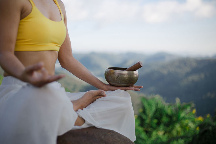 Midsection of woman meditating against sky