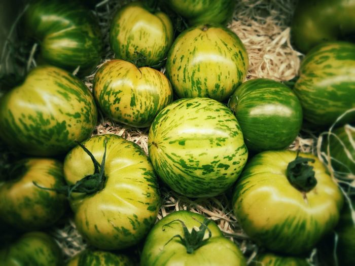 High Angle View Of Green Tomatoes For Sale At Market Stall