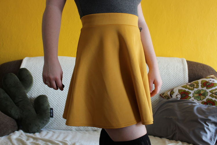 Midsection Of Woman Wearing Yellow Skirt Against Sofa At Home