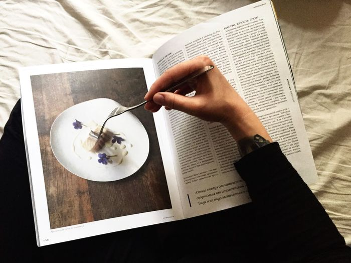 High angle view of woman reading book on table