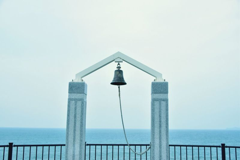Bell Hanging On Structure By Sea Against Clear Sky