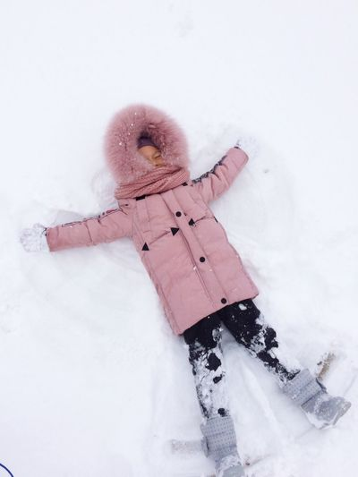 High angle view of girl lying on snow covered field