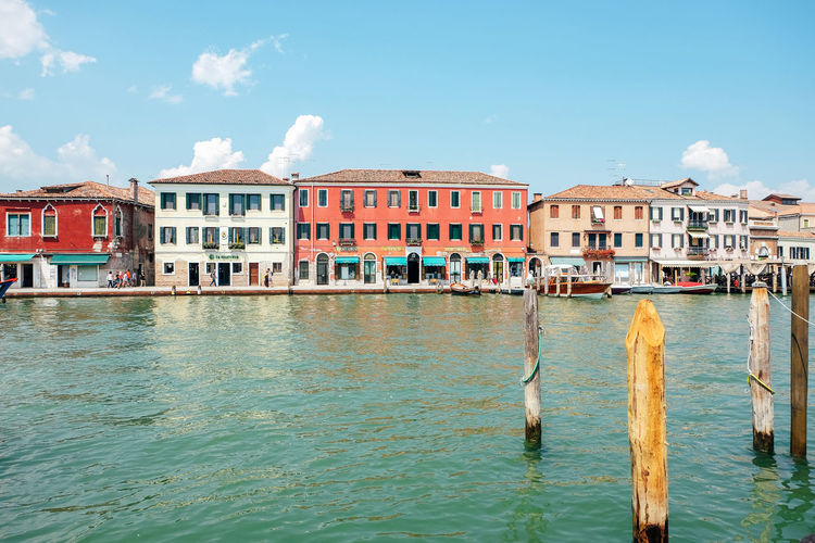 buildings along canal Architecture Building Exterior Built Structure Building Day Outdoors Venice Italy Burano Murano City Summer Water Sky Waterfront Cloud - Sky Nature Residential District No People Canal House Rippled Wood - Material Sea Wooden Post