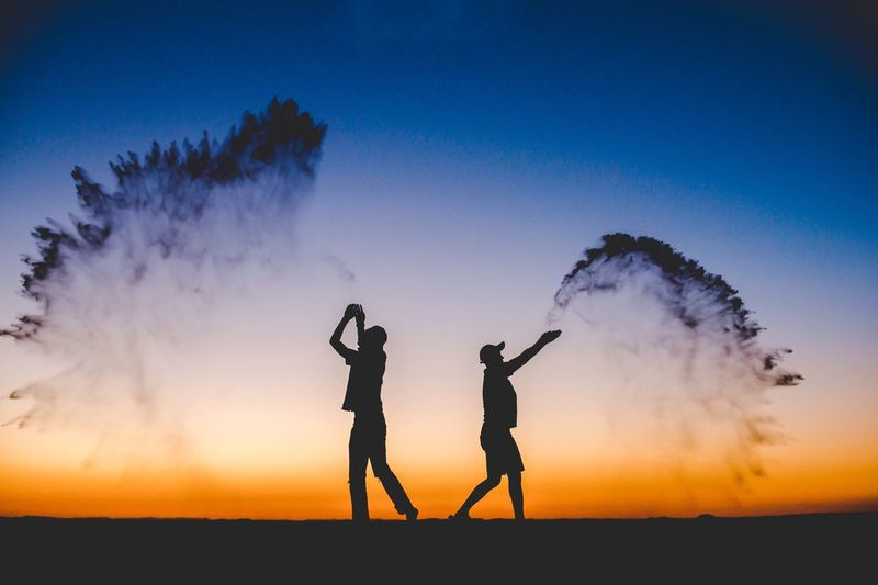 Silhouette men throwing dust against sky during sunset