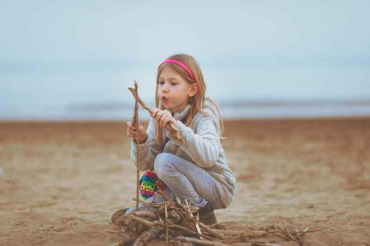 Girl playing with wood while kneeling at beach