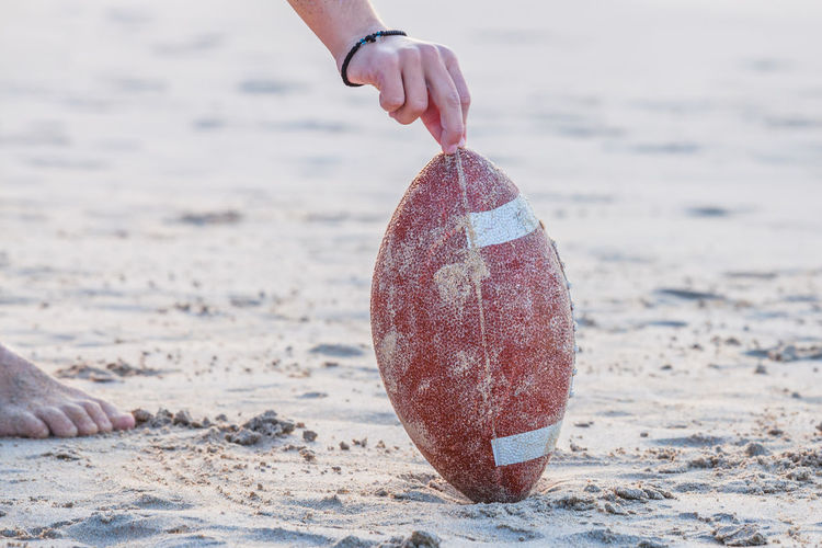 Cropped Image Of Man Holding Rugby Ball At Beach
