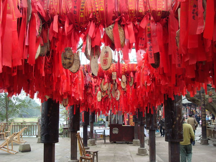 Low angle view of red japanese fortune ribbons hanging at shrine