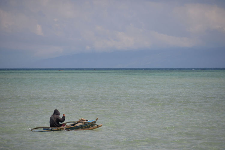 Rear view of man sitting in boat on sea against cloudy sky