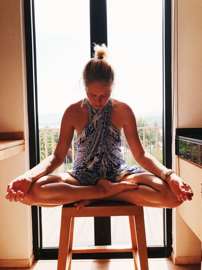 Woman meditating while sitting against window at home