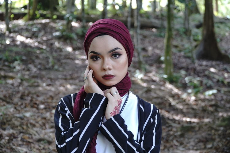 Portrait of beautiful woman wearing hijab, vintage fashion at green nature park. One Person Young Adult Lifestyles Front View Young Women Beautiful Woman Outdoors Portrait Looking At Camera Focus On Foreground Standing Headshot Real People Casual Clothing Women Adult Leisure Activity Beauty Lipstick Dyed Hair Hairstyle Scarf