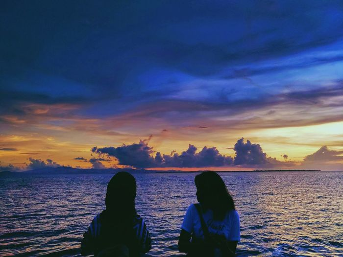 Rear View Of Friends Standing By Sea Against Sky During Sunset