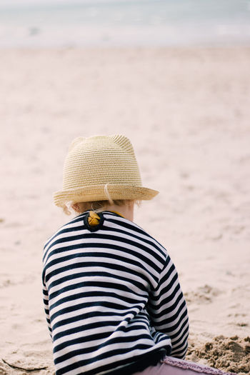 Rear view of person wearing hat on beach