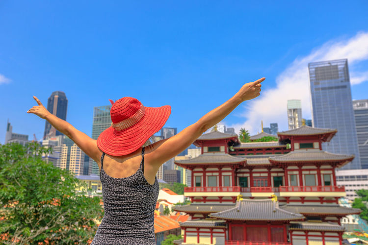 Carefree woman enjoying panoramic views of famous Buddha Tooth Relic Temple in heart of Chinatown, Singapore. Aerial cityscape skyline downtown. Lifestyle tourist with raised arms in a sunny blue sky. Singapore Singapore City Woman Tourist Tourist Attraction  Tourist Destination People Girl Females Aerial View Skyline Cityscape Panorama Happy Travel Hat Lifestyle Enjoy Nature Tourism Buddha Tooth Relic Temple, Singapore Buddha Tooth Relic Temple Temple Buddhist Temple Buddhism Built Structure Architecture Building Exterior One Person Real People Lifestyles Sky Leisure Activity Day Women Human Arm Standing Casual Clothing Building Clothing Blue Waist Up City Outdoors Arms Raised Hairstyle
