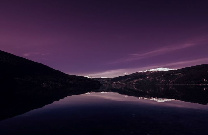 Panoramic View Of Mountains Reflecting On Calm Lake Against Sky At Dusk