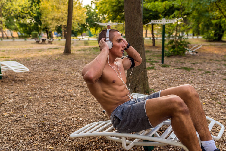 Shirtless man doing sit-ups at park