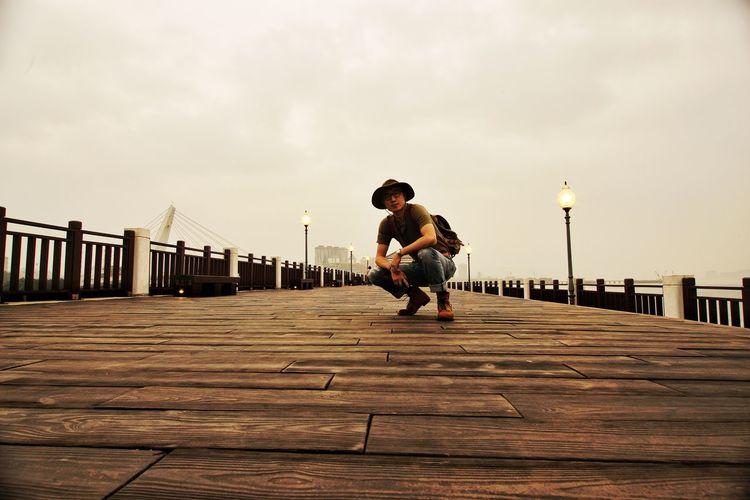 Full length of man on footbridge against sky