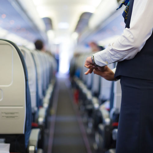 Midsection of cabin crew in airplane