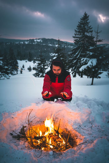 Outdoor shot of young hiker warming his hands above a bonfire. Traveler man sitting near to camping tent in the mountains. Winter Snow Cold Temperature One Person Warm Clothing Real People Nature Clothing Burning Leisure Activity Fire Flame Tree Fire - Natural Phenomenon Beauty In Nature Full Length Lifestyles Front View Land Bonfire Campfire Outdoors Bonfire Hands Warming