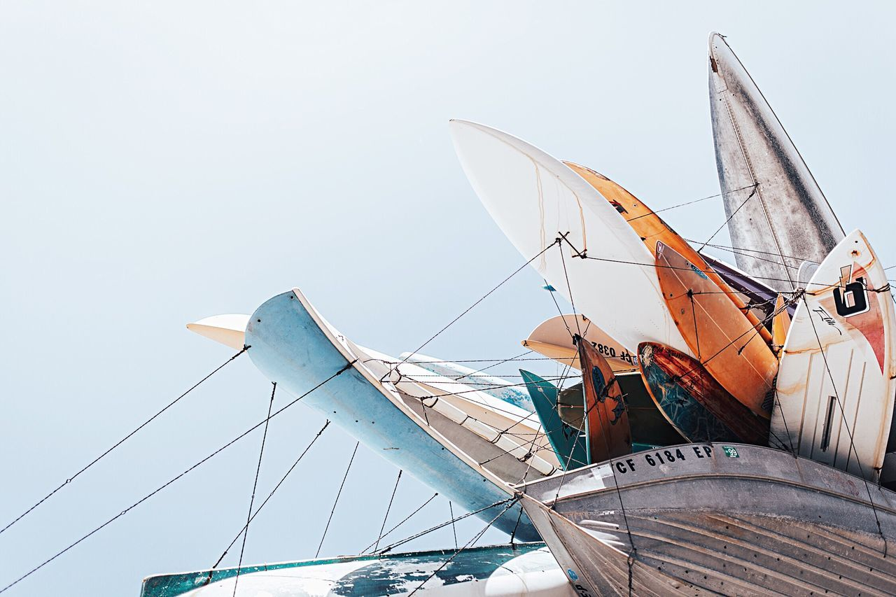 Low angle view of various boats against sky