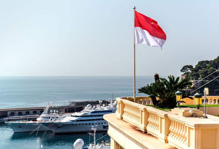 National flag of of the Principality of Monaco and view of port Harbor Marina Mediterranean Sea Monaco Vacations Waving Flag Bay Europe Famous Place Flag Landmark Luxury Monte Carlo National Flag Nautical Vessel Outdoors Port Principality Of Monaco Sea Seaside Sunny Day Tourism Tourist Resort Travel Destinations Yacht