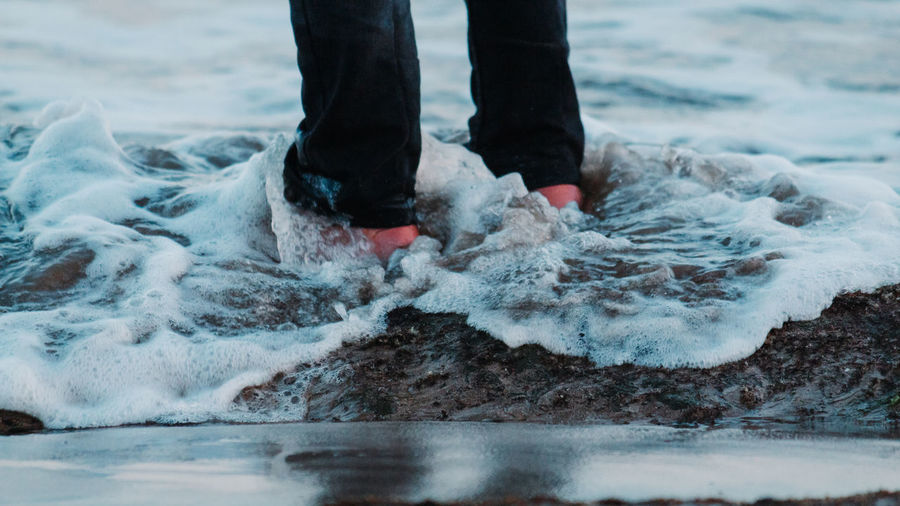 Low section of person standing on sea shore