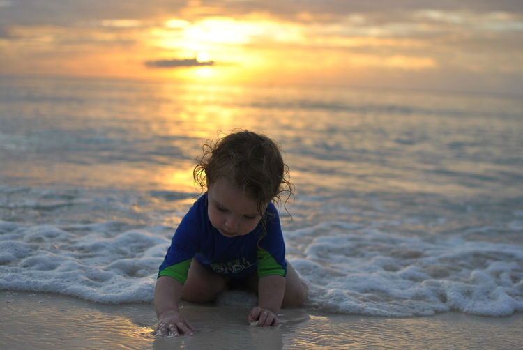 Girl playing with water at beach against sky during sunset