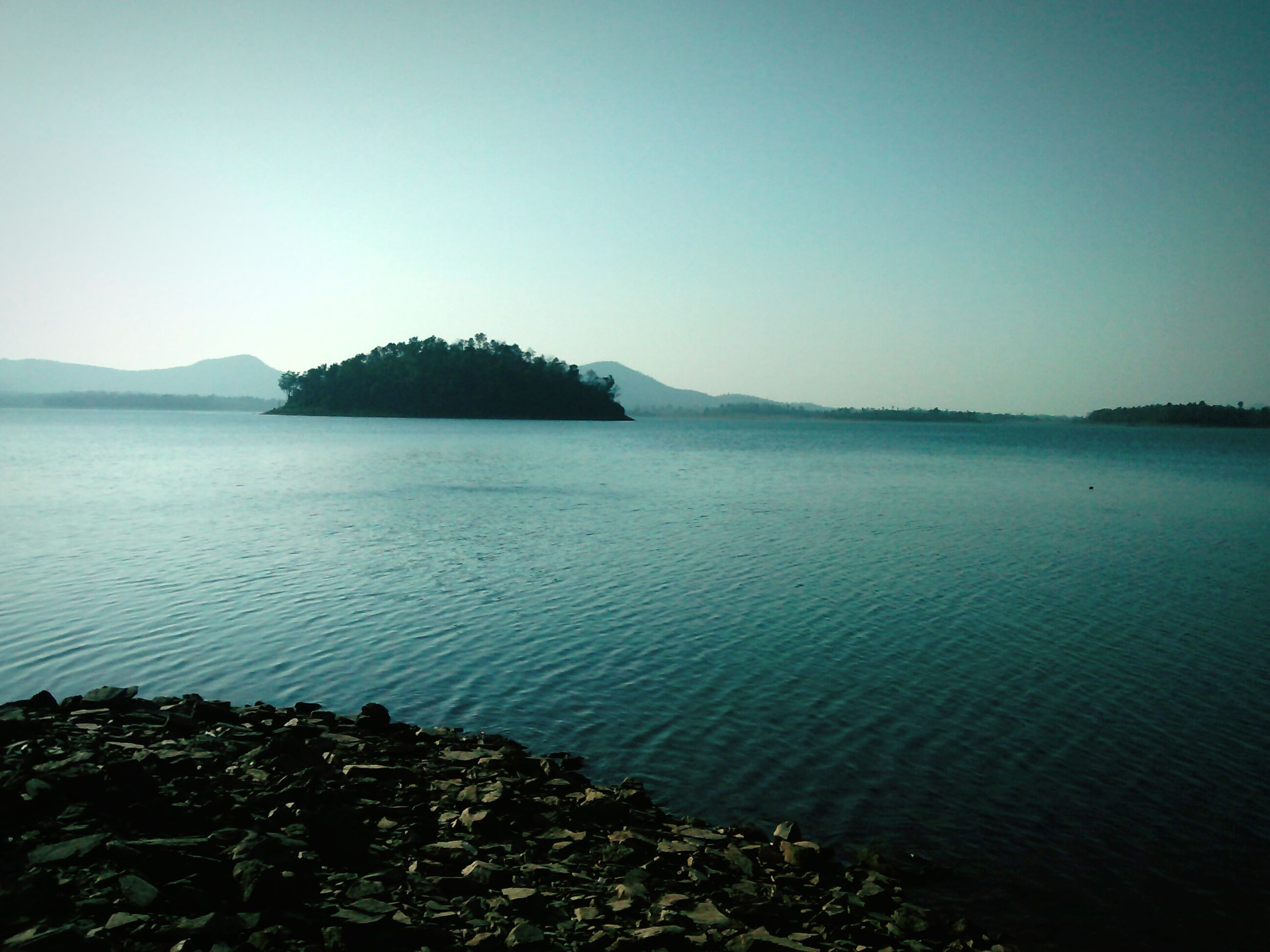 water, clear sky, tranquil scene, tranquility, scenics, beauty in nature, sea, copy space, nature, blue, mountain, idyllic, rippled, lake, coastline, non-urban scene, calm, outdoors, day, remote