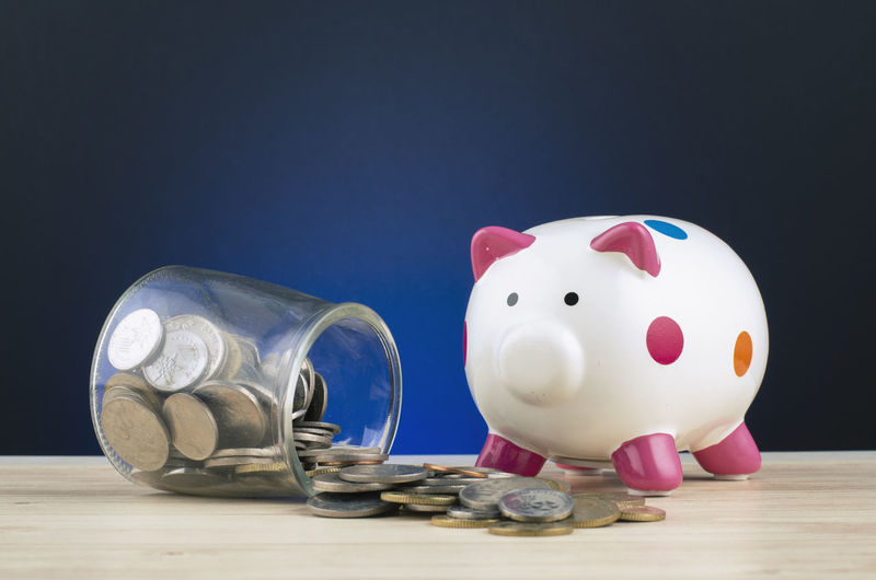 piggy bank with coins in glass jar on wooden desk spilling out Investment Finance Savings Piggy Bank Indoors  Studio Shot Currency Still Life Table Coin Blue Wealth Copy Space Business Large Group Of Objects No People Close-up Animal Representation Container Representation Black Background Coin Bank Economy Blue Background