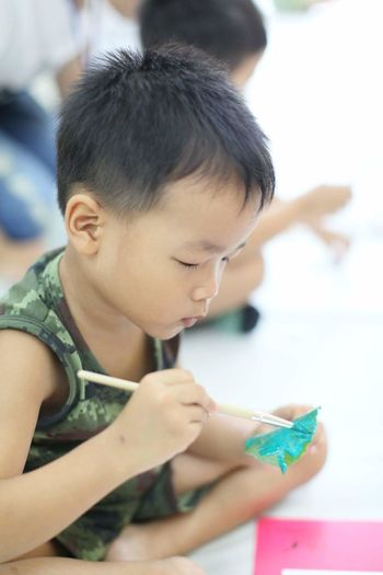 Boy painting object