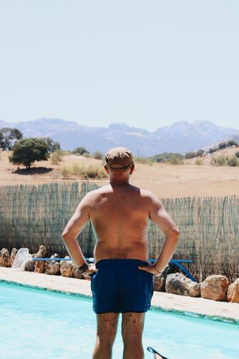 Rear view of shirtless man standing in swimming pool against sky