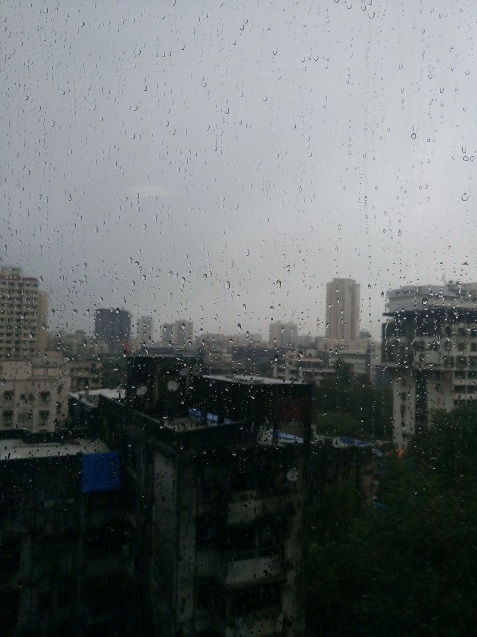 wet, drop, rain, weather, rainy season, raindrop, architecture, window, glass - material, building exterior, built structure, no people, water, city, sky, day, skyscraper, outdoors, cityscape, clear sky, nature