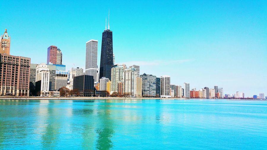 Chicago river against modern buildings against blue sky