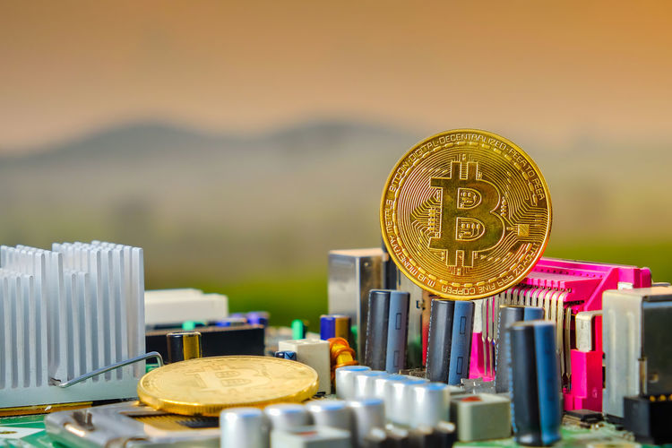 Bitcoin with a motherboard, Golden Bitcoin Cryptocurrency on computer circuit board with blurred green nature while sunrise. The concept of cryptocurrency. Blockchain technology. Architecture Business Close-up Coin Currency Day Economy Finance Focus On Foreground Food Food And Drink Gold Colored Large Group Of Objects Metal No People Outdoors Selective Focus Still Life Table Wealth