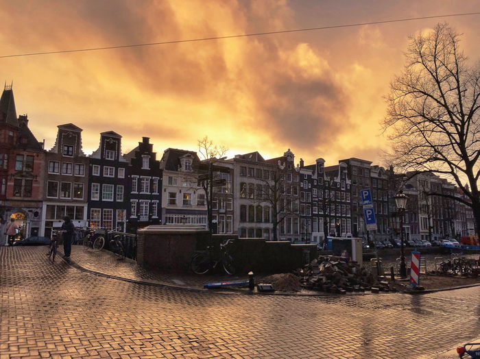 Sunset City Cityscape Sky Cloud - Sky Sunlight Golden Hour Nature City Life Building Exterior Architecture Built Structure Building Street Residential District Outdoors Evening After The Rain Rainy Days Travel Travel Destinations Europe Streetphotography Mode Of Transportation