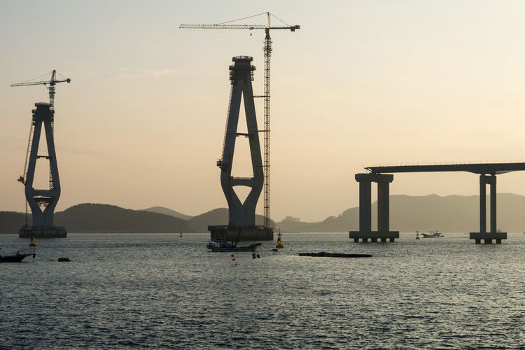Incomplete bridge columns by cranes amidst sea against sky during sunset