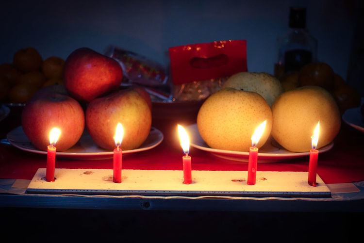 Burning Candles With Fruits On Table