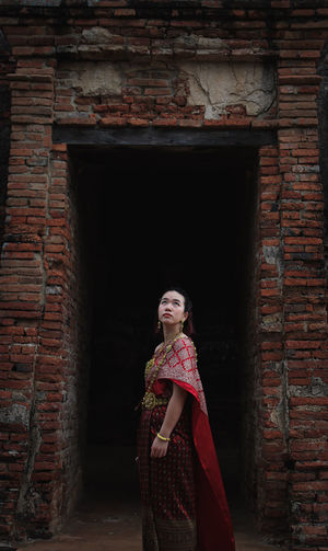Side view of woman standing in traditional clothing against brick wall