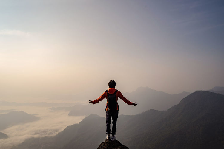 Rear view of carefree backpacker with arms outstretched looking at landscape while standing on mountain during foggy weather