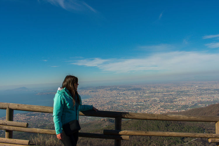 Mid adult woman standing by railing on observation point against blue sky during sunny day