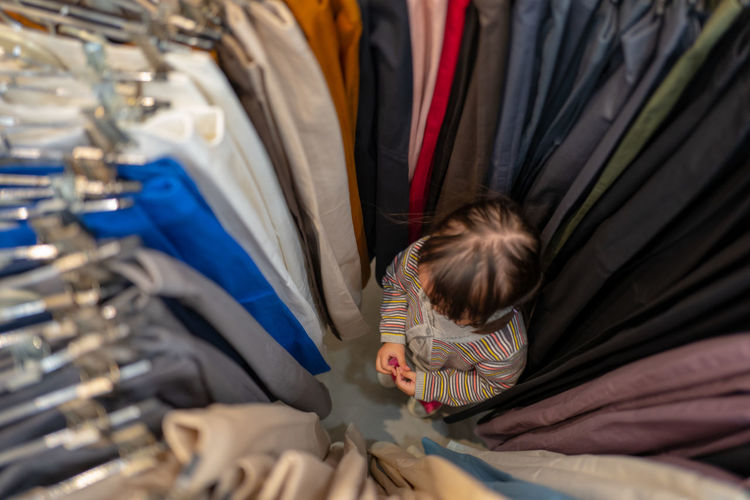 High angle view of girl standing amidst clothes rack